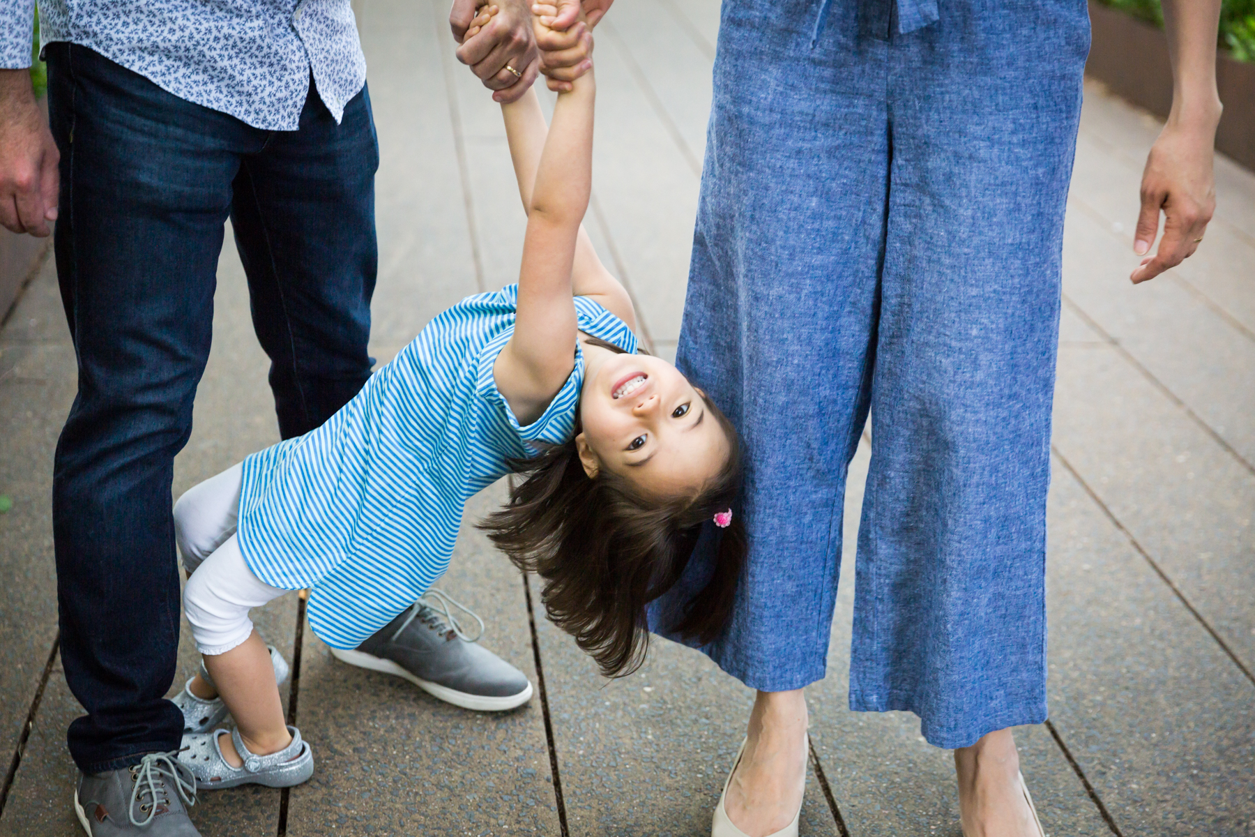 Little girl holding parents' hands for an article on High Line family portrait tips