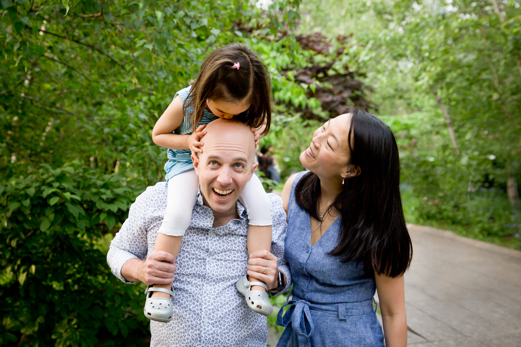 Little girl kissing father's head for an article on High Line family portrait tips