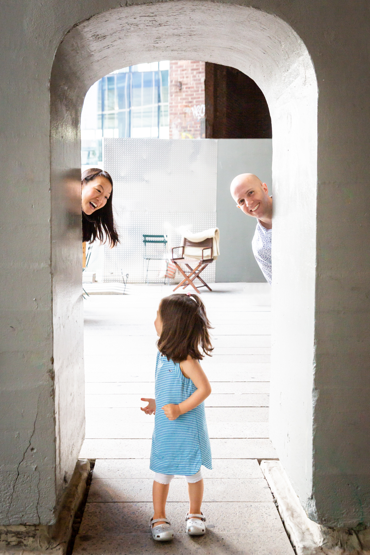 Parents playing peek-a-boo with little girl for an article on High Line family portrait tips
