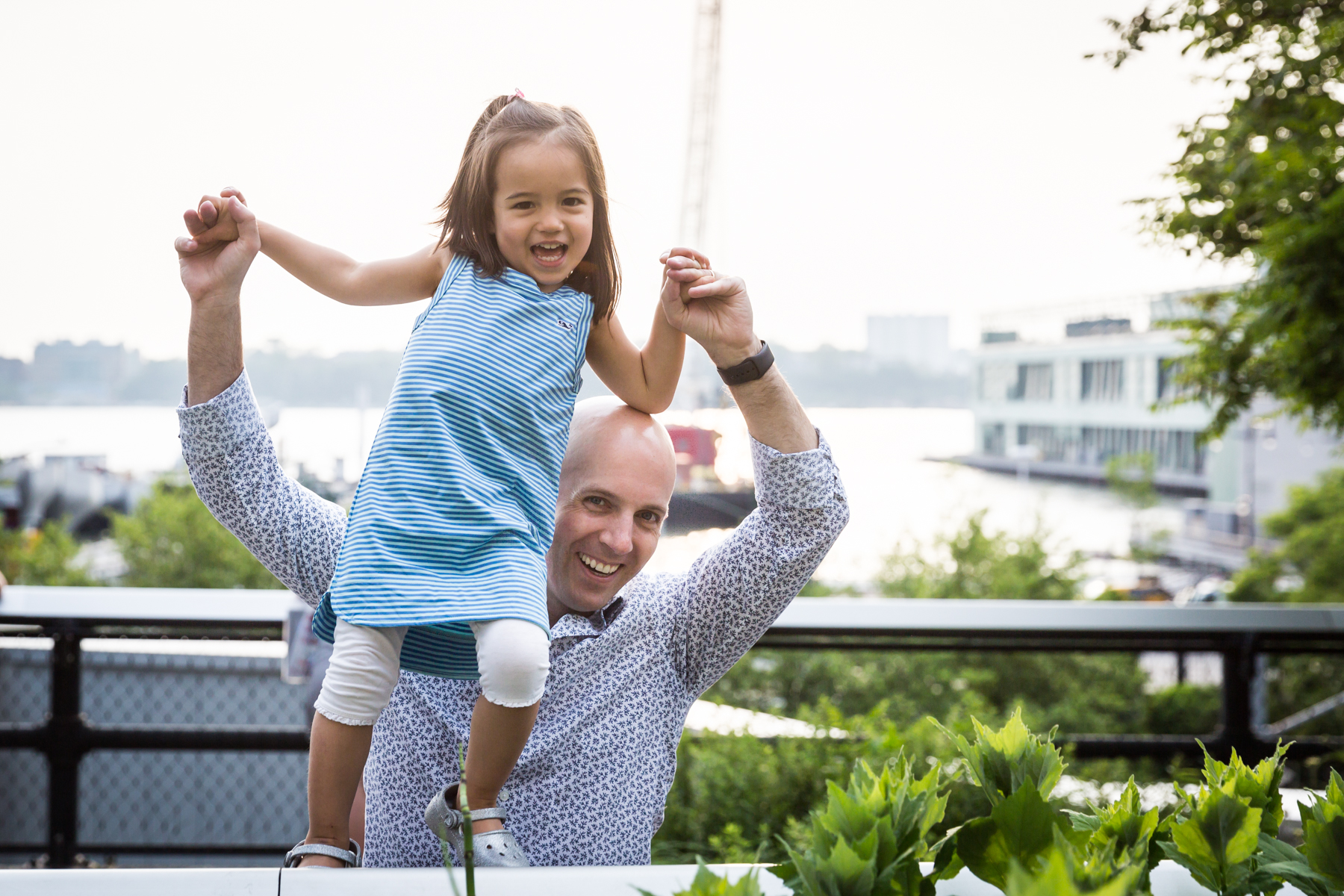 Father holding up little girl for an article on High Line family portrait tips