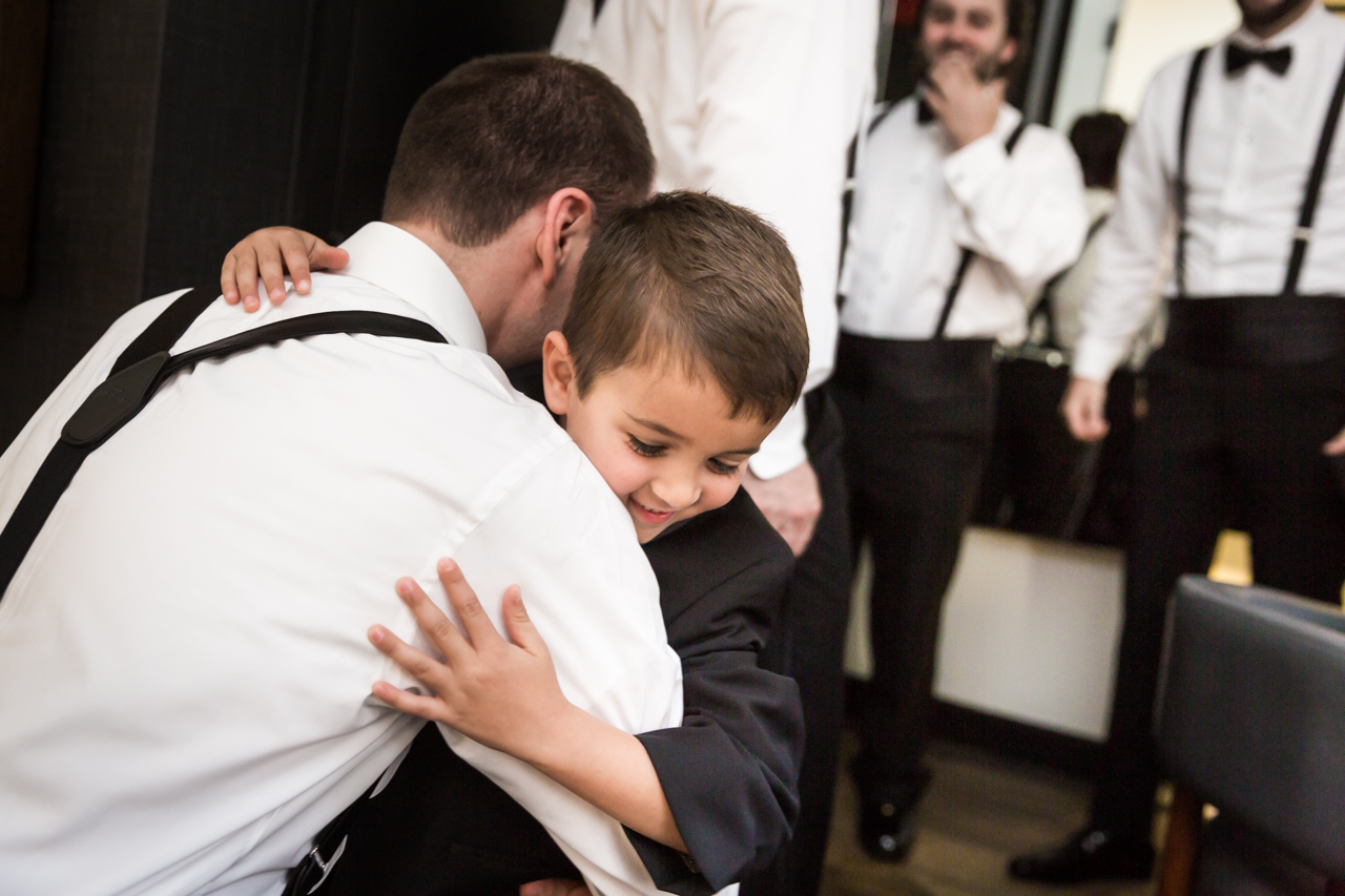 Ring bearer giving groom a hug at a Central Park Conservatory Garden wedding