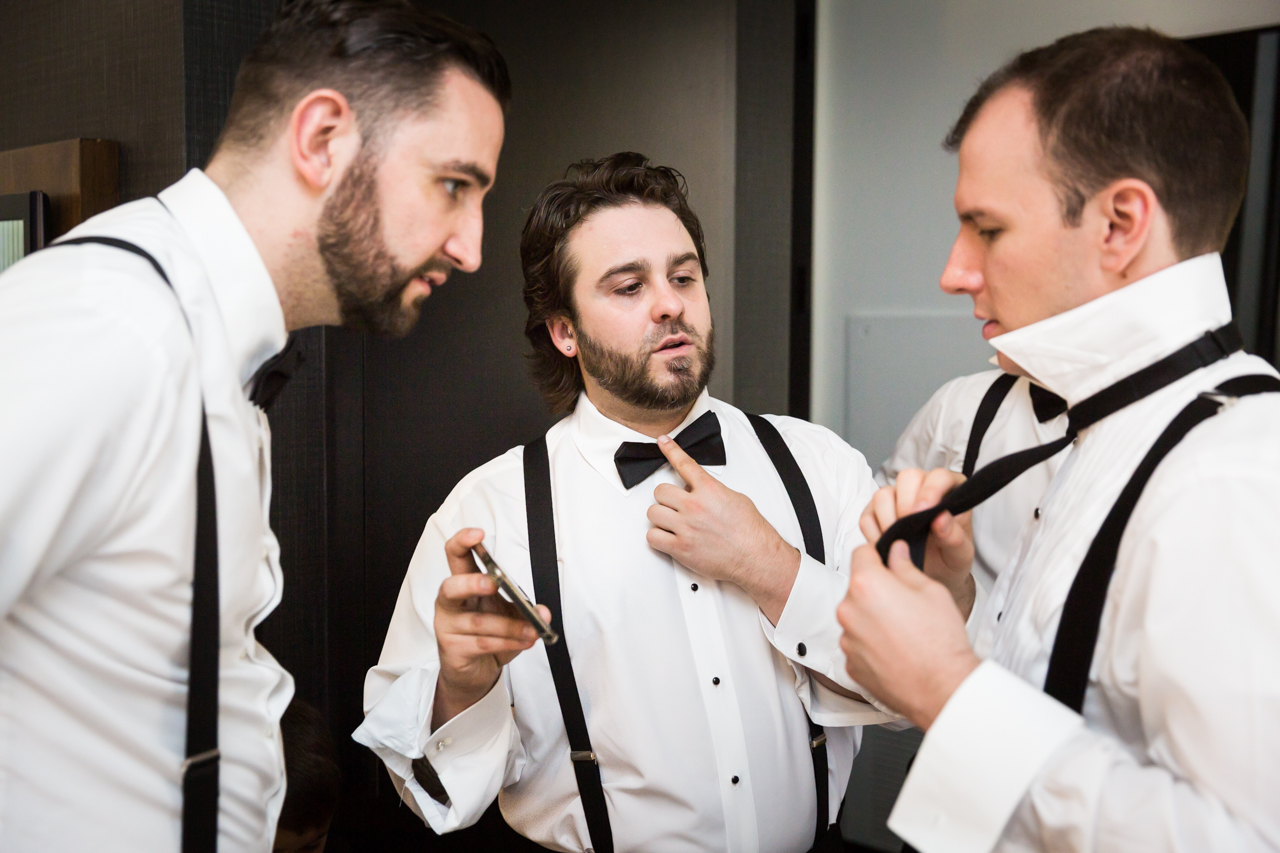 Groom and groomsmen trying to tie bowtie at a Central Park Conservatory Garden wedding