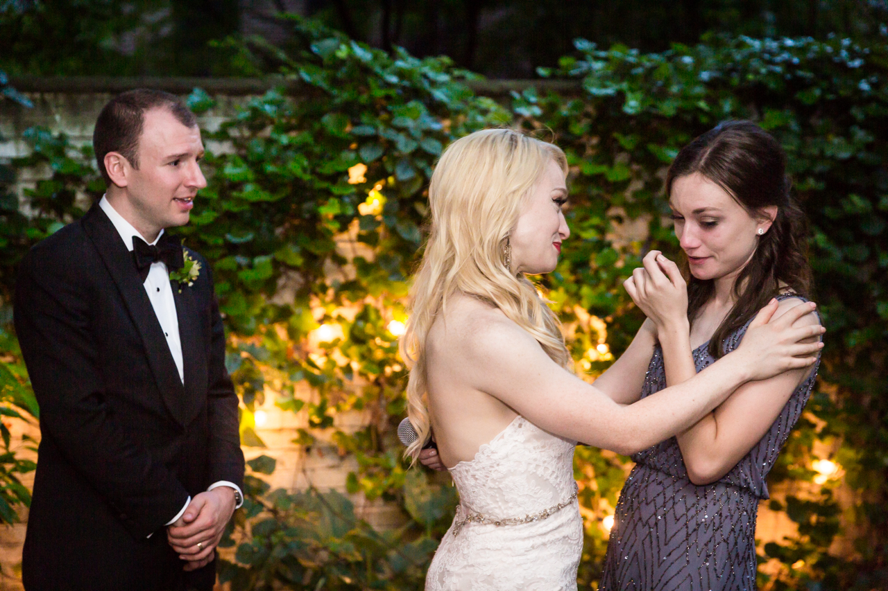 Bride comforting bridesmaid after toast at a Central Park Conservatory Garden wedding