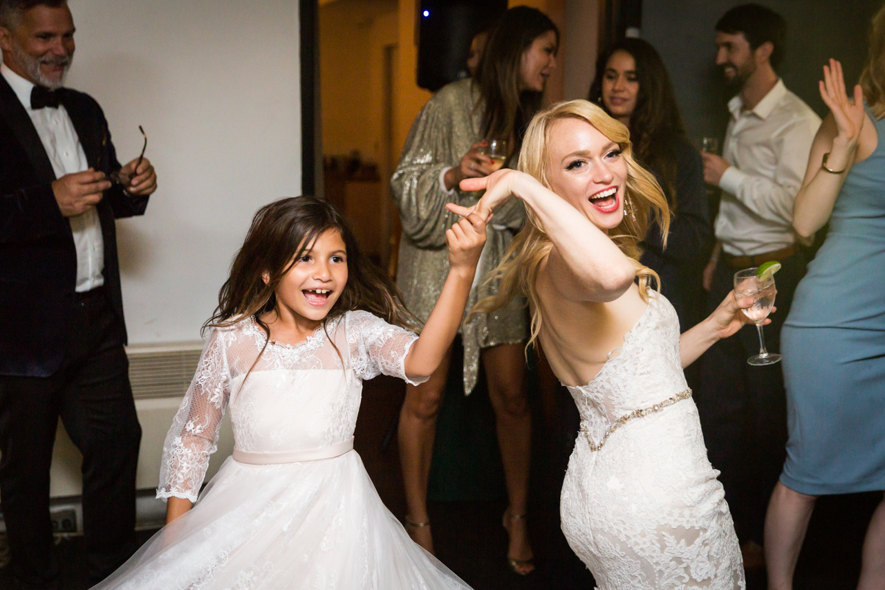 Bride and little girl dancing at a Central Park Conservatory Garden wedding