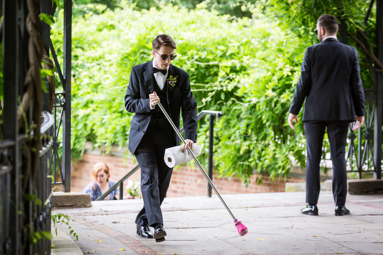 Groomsmen sweeping floor at a Central Park Conservatory Garden wedding