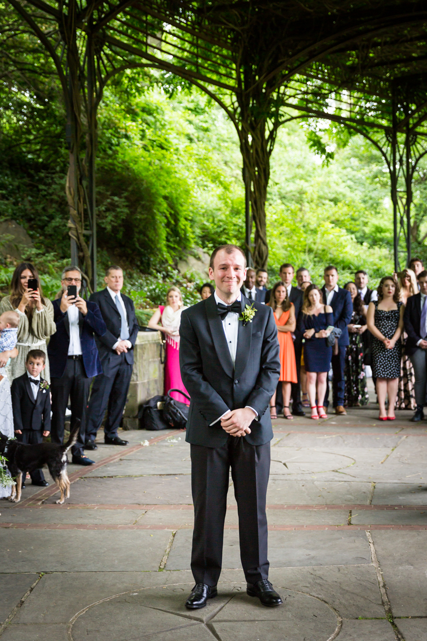 Groom waiting for bride at end of aisle at a Central Park Conservatory Garden wedding