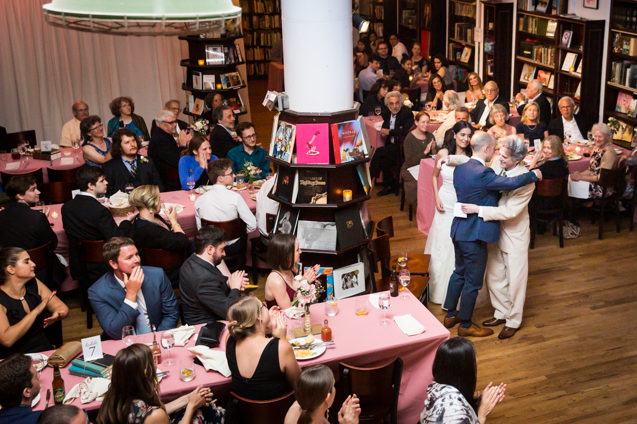 Bride and groom hugging speaker at reception