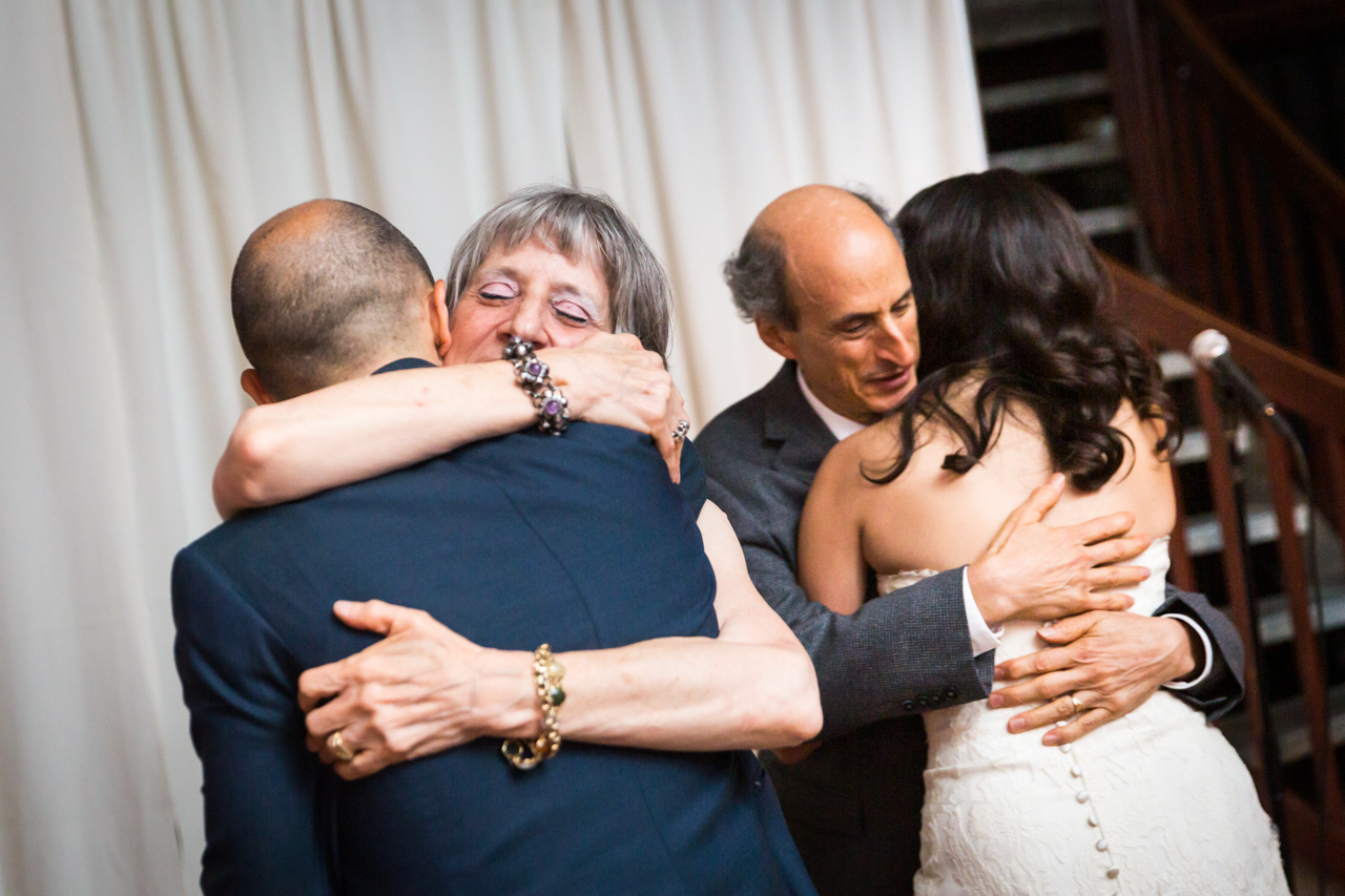 Bride and groom hugging parents for an article on non-floral centerpiece ideas