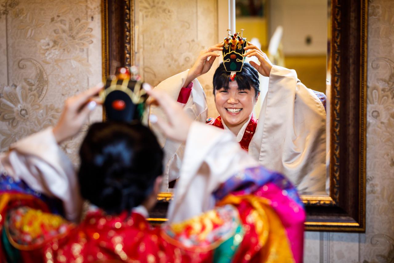 Bride adjusting jokduri at traditional Korean pyebaek ceremony
