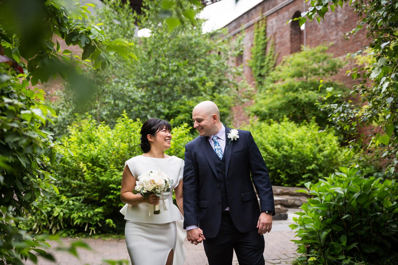 Bride and groom walking close in Brooklyn Bridge Park