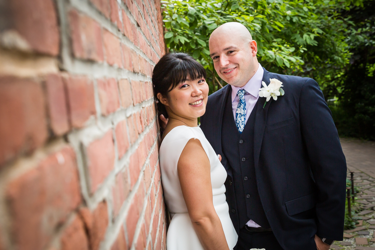 Bride and groom looking into camera against brick wall
