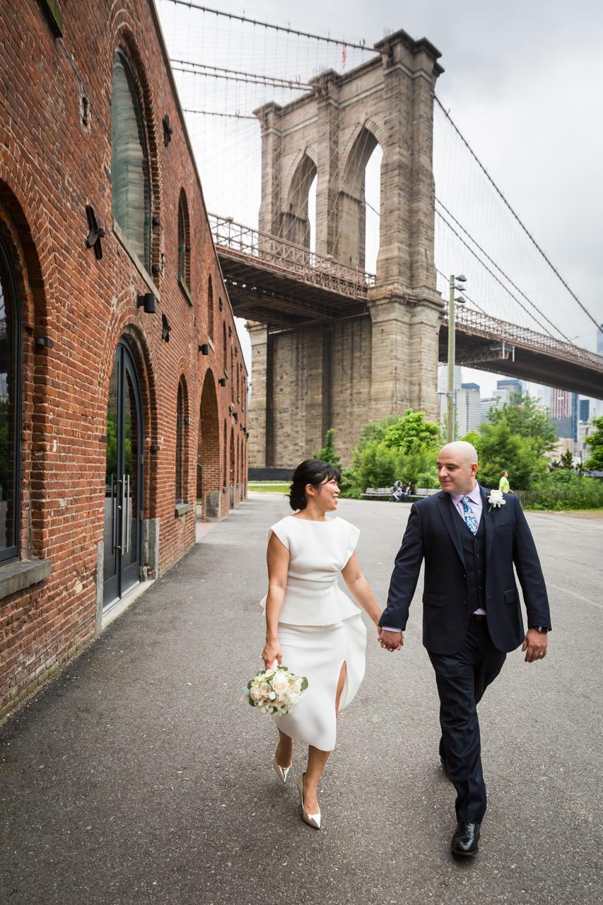 Bride and groom walking in front of Brooklyn Bridge