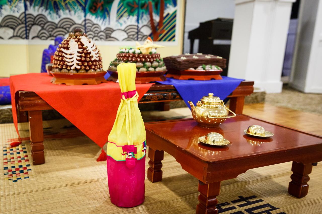 Tea set, jujubes, chestnuts, and rice wine bottle at traditional Korean pyebaek ceremony