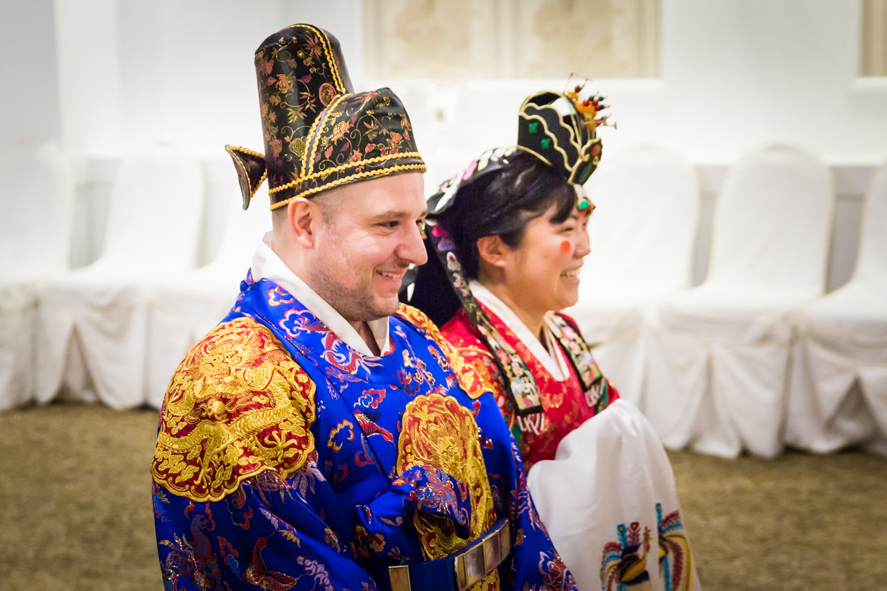 Bride and groom laughing at traditional Korean pyebaek ceremony