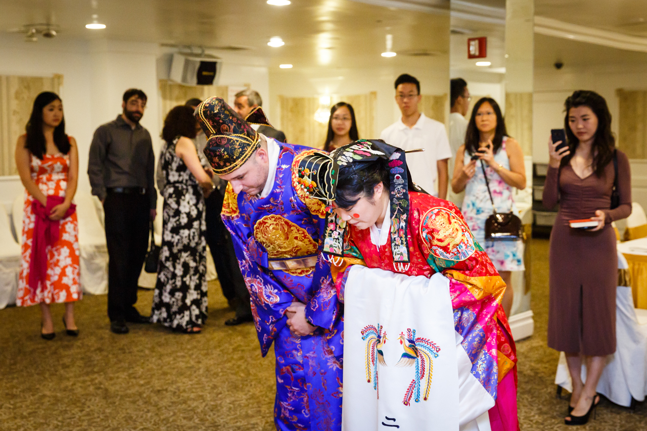Bride and groom bowing at traditional Korean pyebaek ceremony