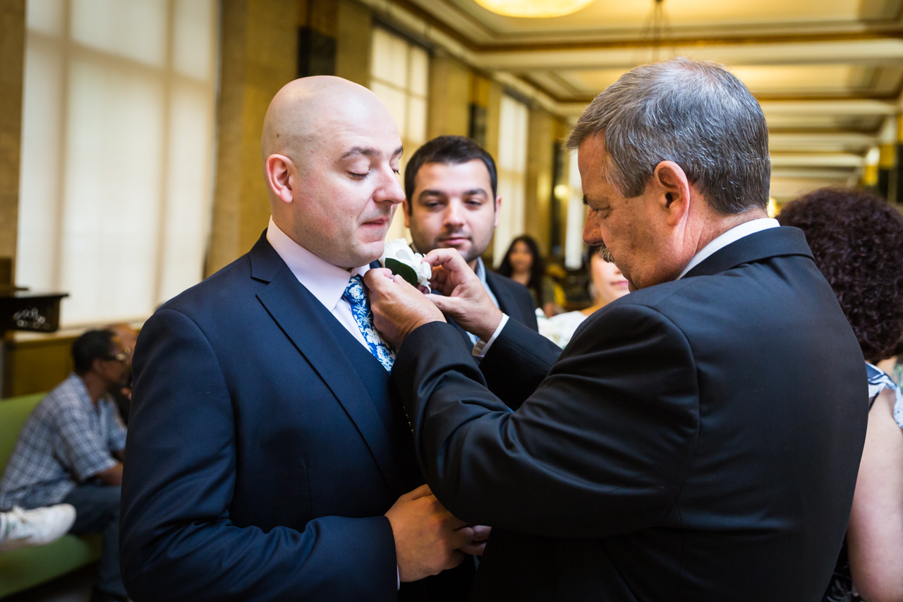 Father adjusting groom's boutonniere