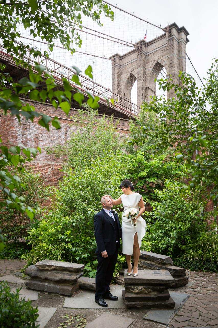 Bride standing on stone steps with groom in Brooklyn Bridge Park