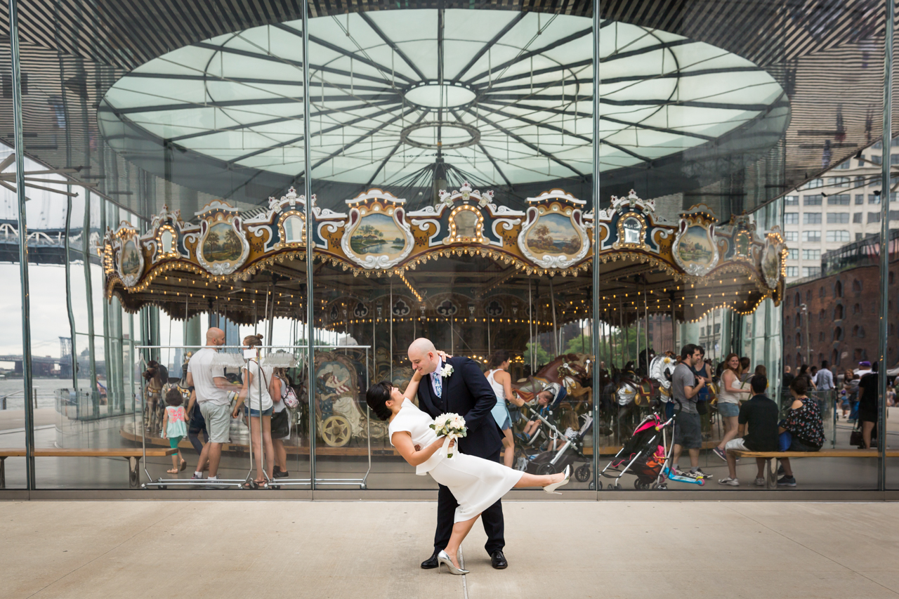 Bride and groom dancing in front of Jane's Carousel in Brooklyn Bridge Park