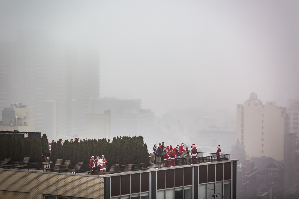 Group of SantaCon participants on hotel rooftop with fog