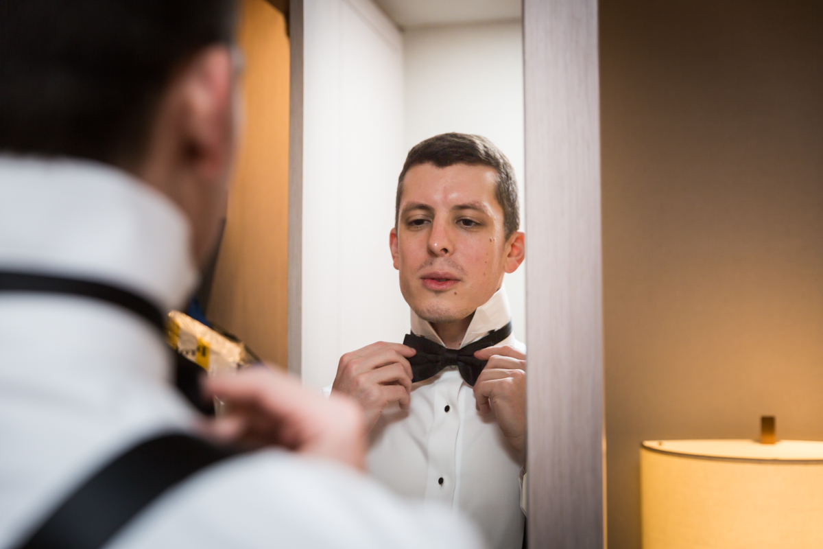 Groom adjusting his bow tie before a Four Seasons Hotel New York Downtown wedding