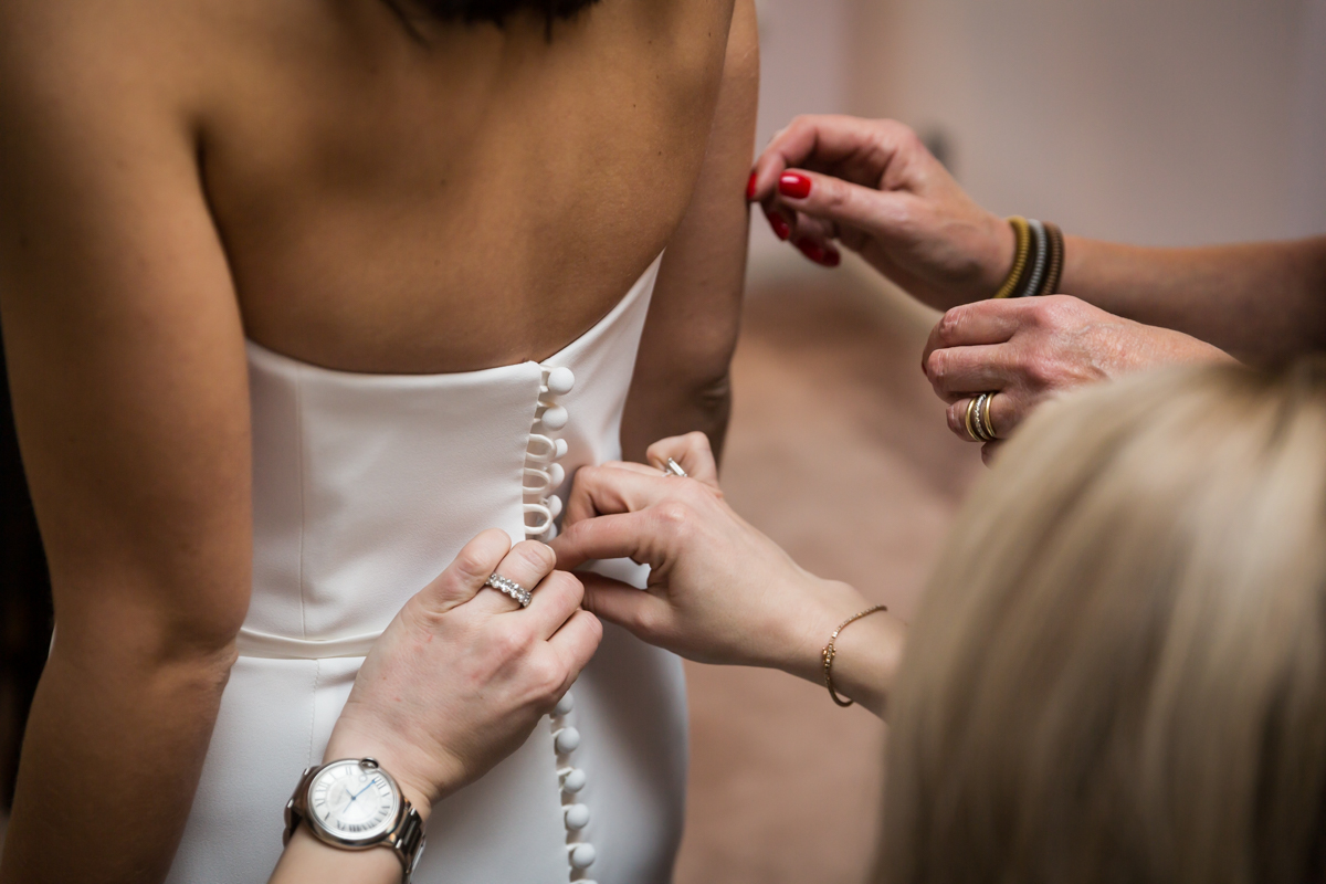 Hands closing buttons on a bride's wedding dress