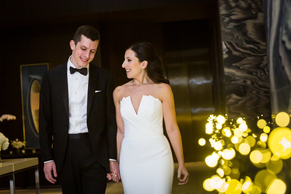 Bride and groom walking down hallway of Four Seasons Hotel New York Downtown