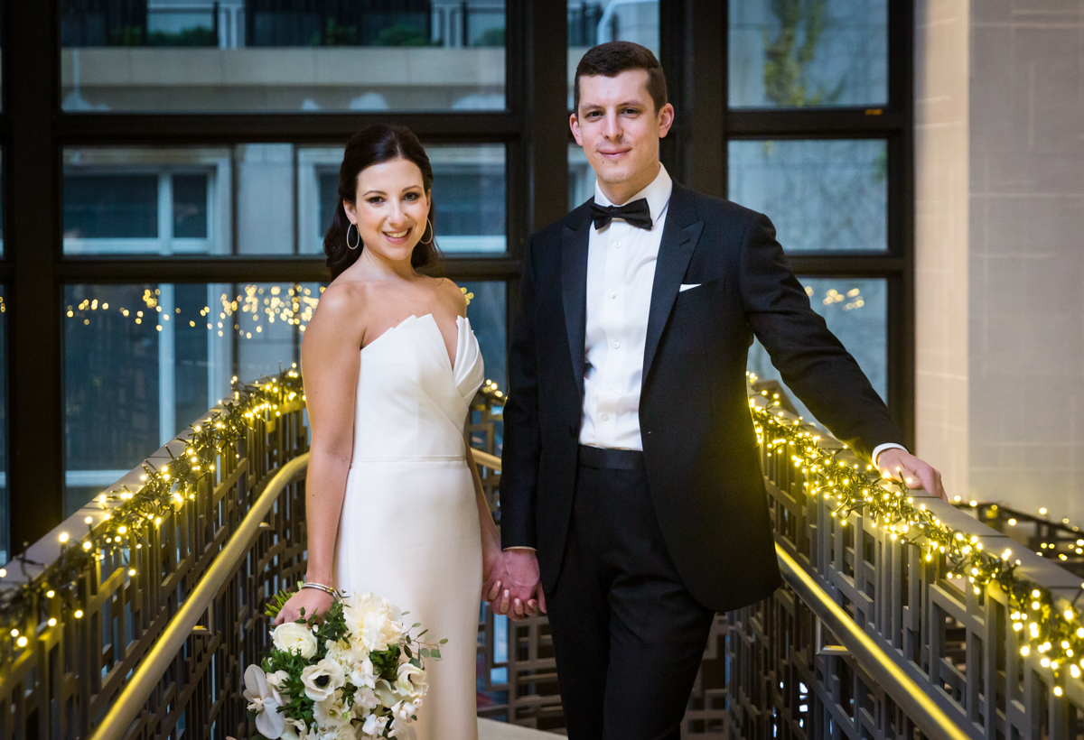 Bride and groom posed on staircase of Four Seasons Hotel New York Downtown