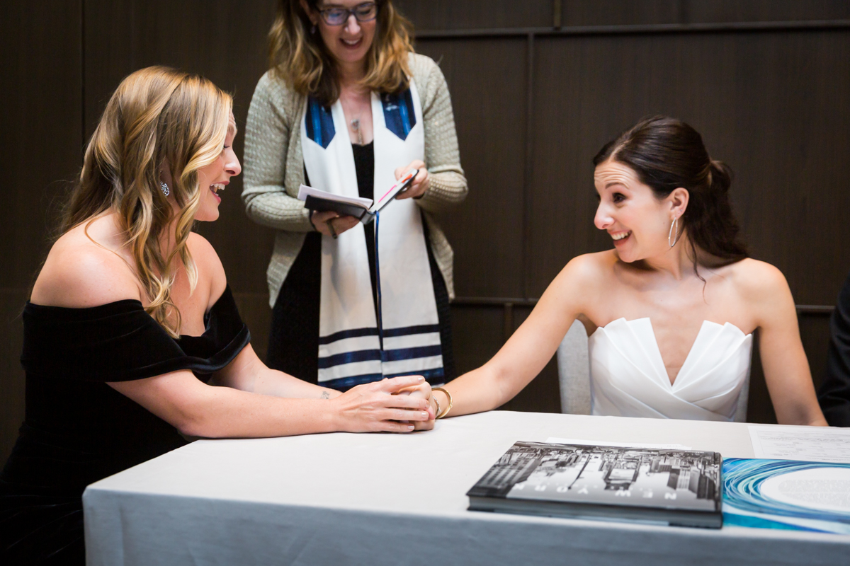 Bride and bridesmaid holding hands during ketubah signing at a Four Seasons Hotel New York Downtown wedding