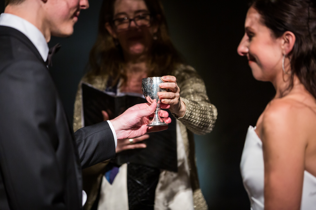Cantor handing kiddush cup to groom during Four Seasons Hotel New York Downtown wedding