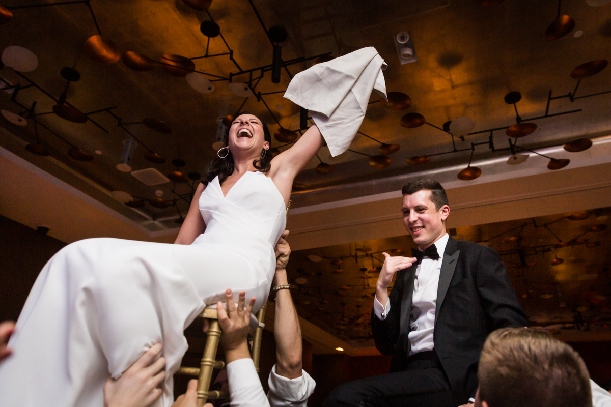 Bride and groom lifted in chairs during hora dance at a Four Seasons Hotel New York Downtown wedding