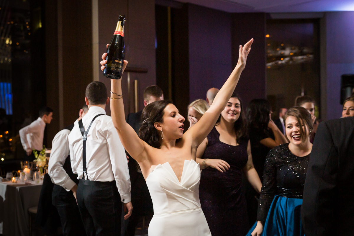 Bride holding up bottle of champagne at wedding reception