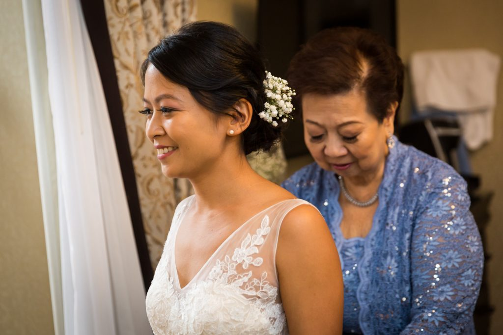 Mother helping bride into wedding dress before Bronx Zoo wedding
