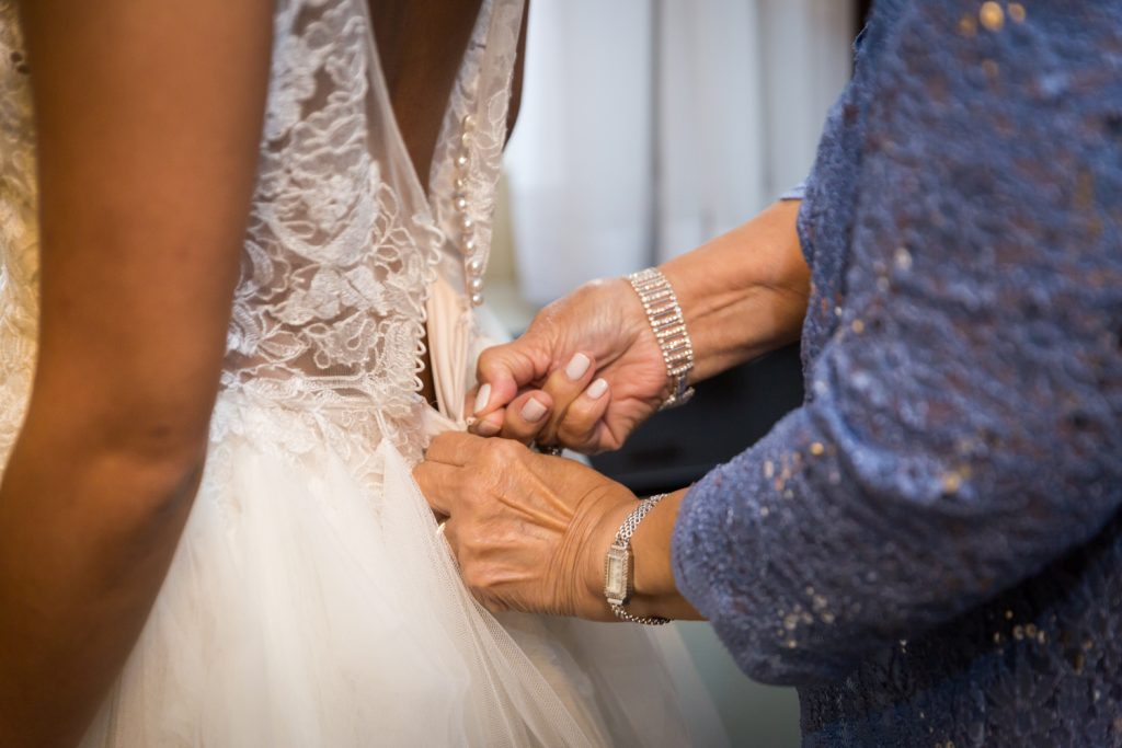 Close up on mother's hands zipping up bride's wedding dress