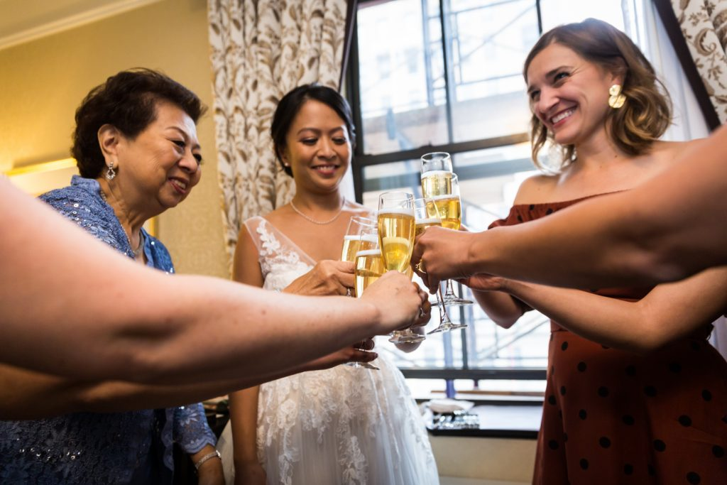 Bride, mother, and bridesmaids toasting with glasses of champagne