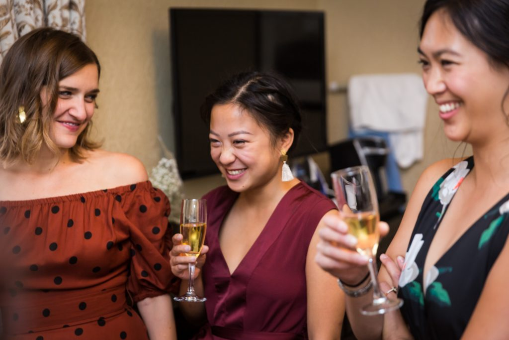 Bridesmaids laughing and holding champagne before Bronx Zoo wedding