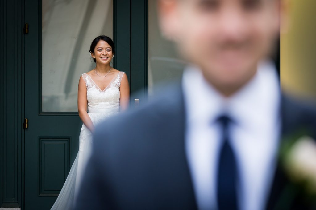 Bride watching groom during first look at Bronx Zoo wedding