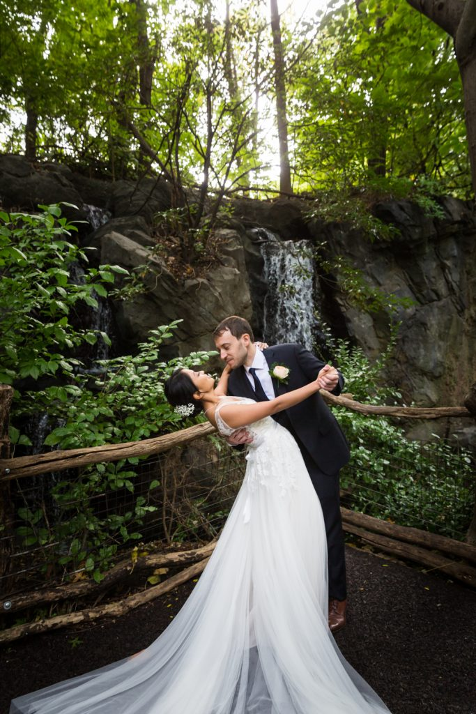 Bride and groom dancing in front of waterfall at Bronx Zoo Congo Gorilla Forest exhibit