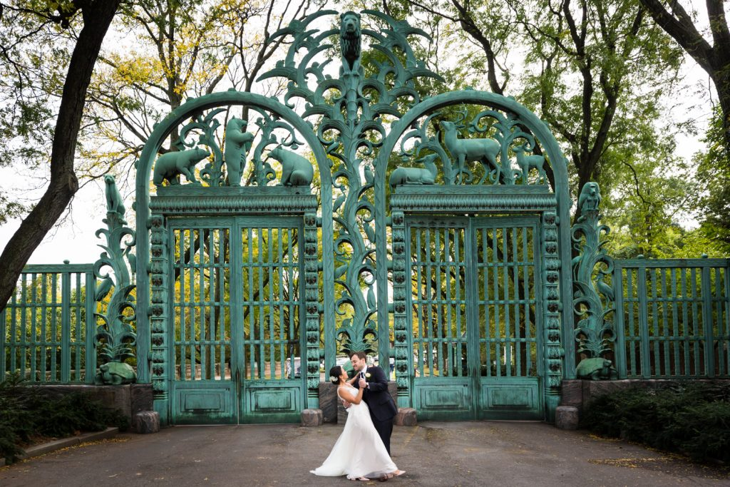 Groom dipping bride in front of Bronx Zoo gates