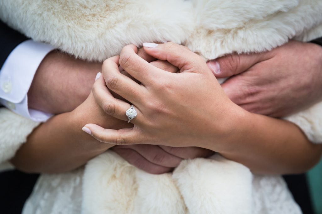 Close up of bride's hands with engagement ring