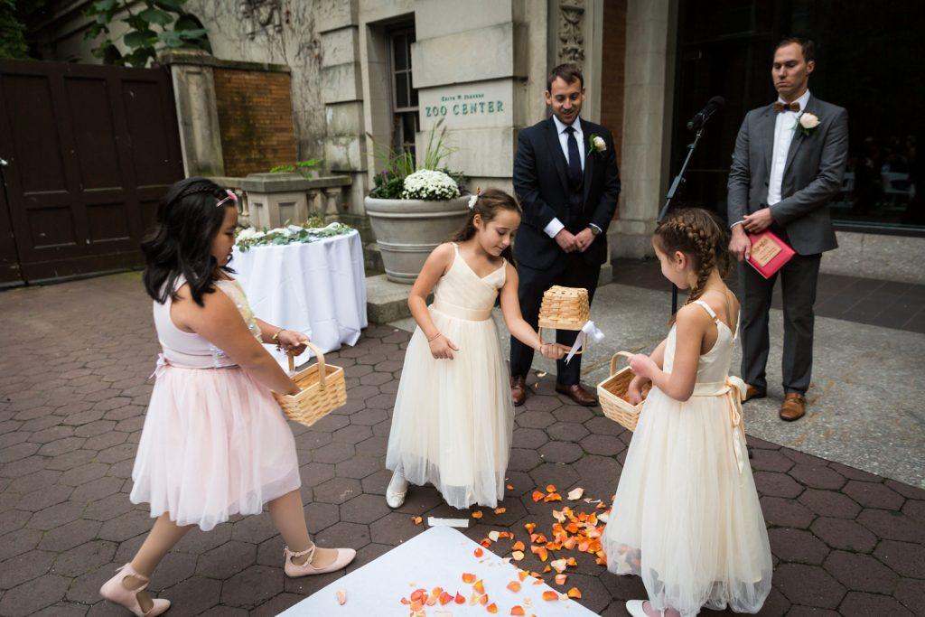 Three flower girls dumping flowers at Bronx Zoo wedding ceremony
