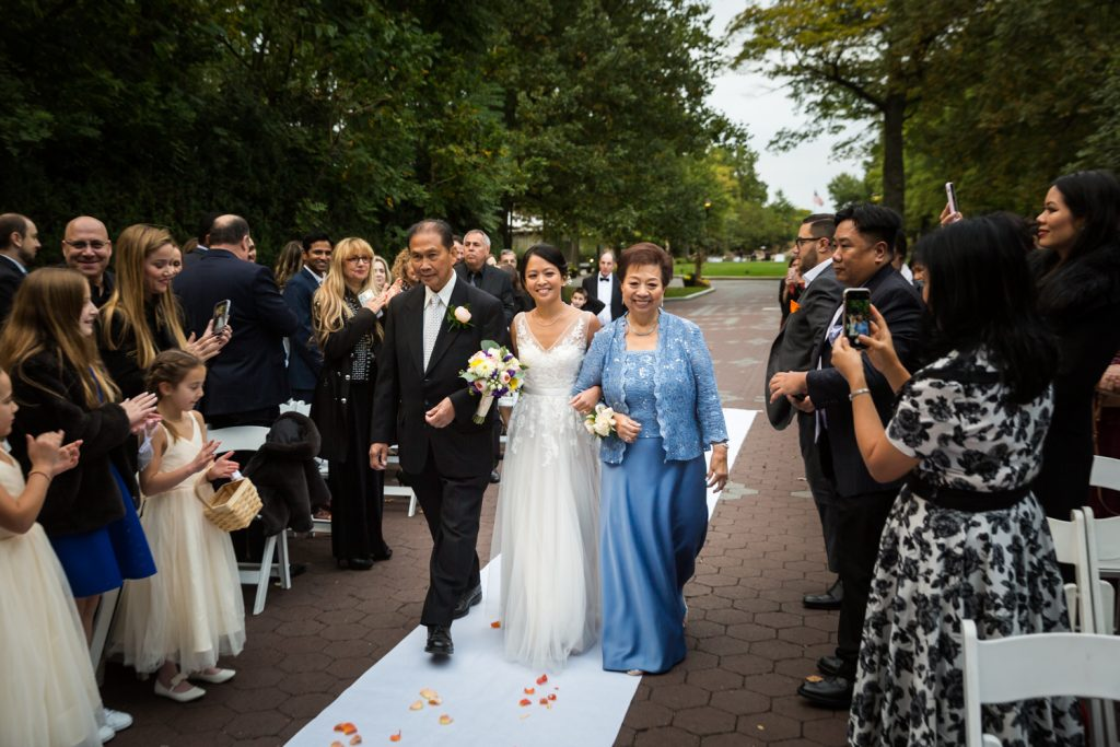 Bride walking down aisle with both parents at Bronx Zoo wedding