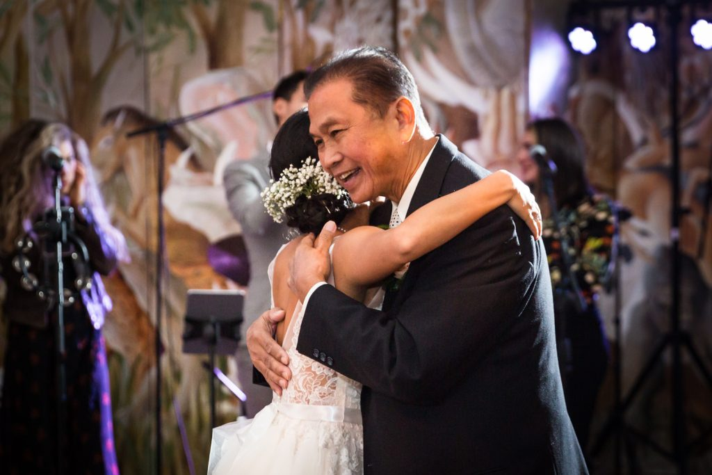 Father embracing bride at Bronx Zoo wedding