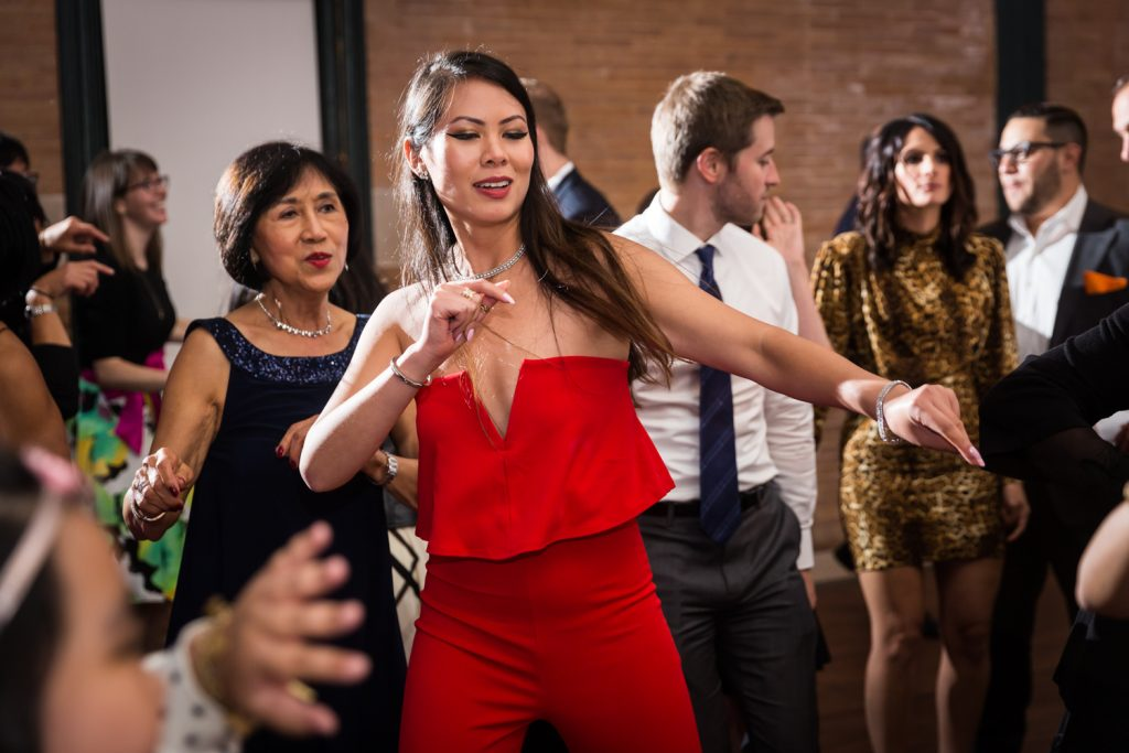 Woman in red jumpsuit dancing at Bronx Zoo wedding reception