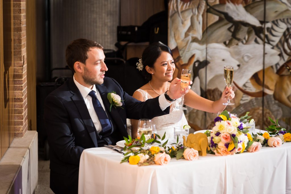 Bride and groom holding up glasses of champagne at a Bronx Zoo wedding