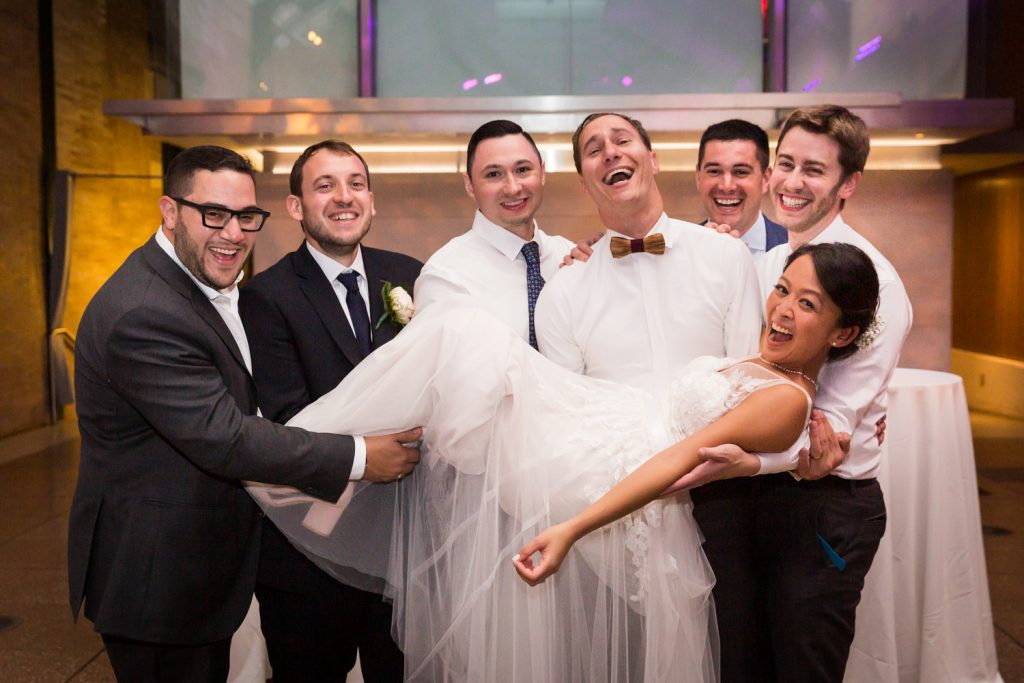 Bride lifted in the air by groomsmen at at Bronx Zoo wedding