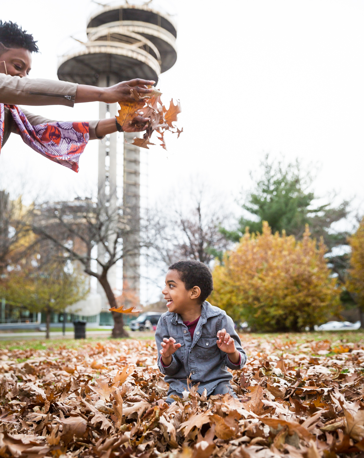 Flushing Meadows Corona Park family portrait of mother dropping leaves on little boy