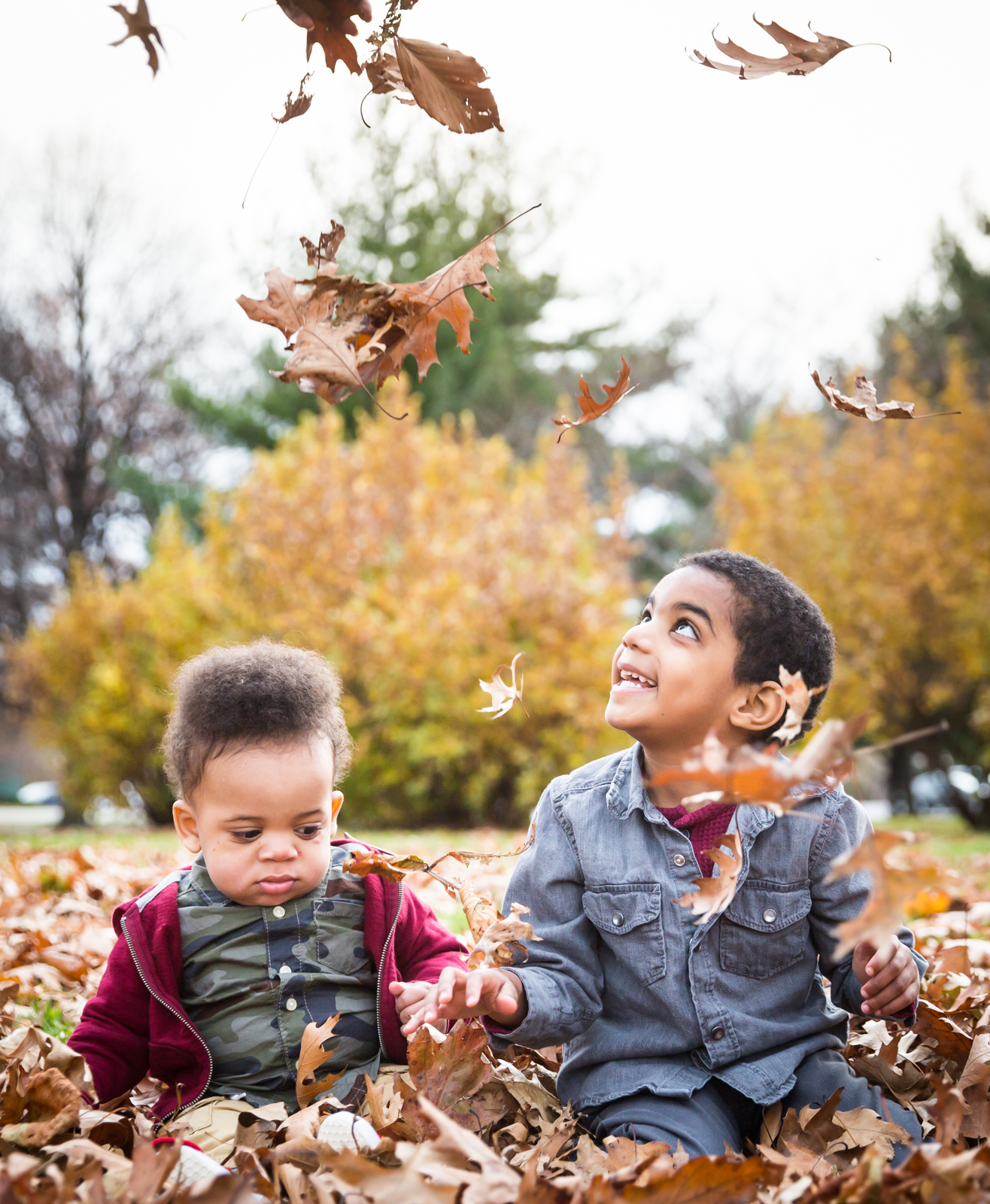 Flushing Meadows Corona Park family portrait of two little boys playing in fall leaves