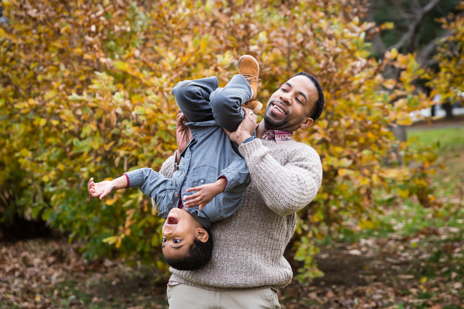 Flushing Meadows Corona Park family portrait of father holding son upside down