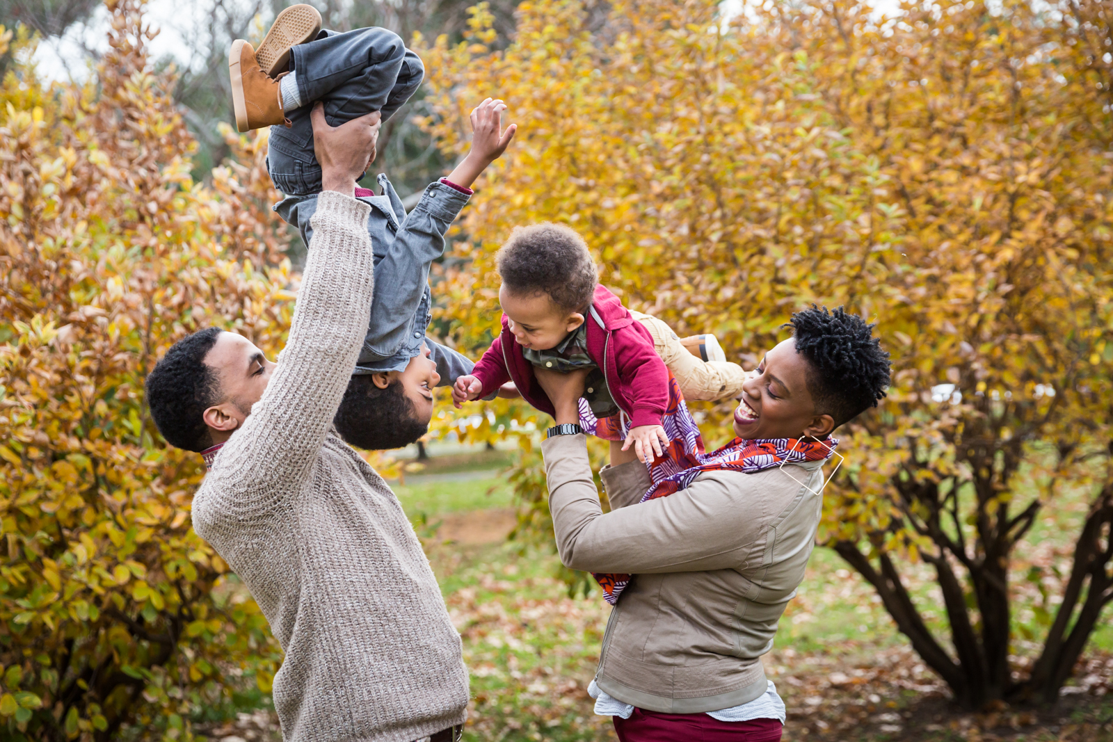 Flushing Meadows Corona Park family portrait of parents holding up children