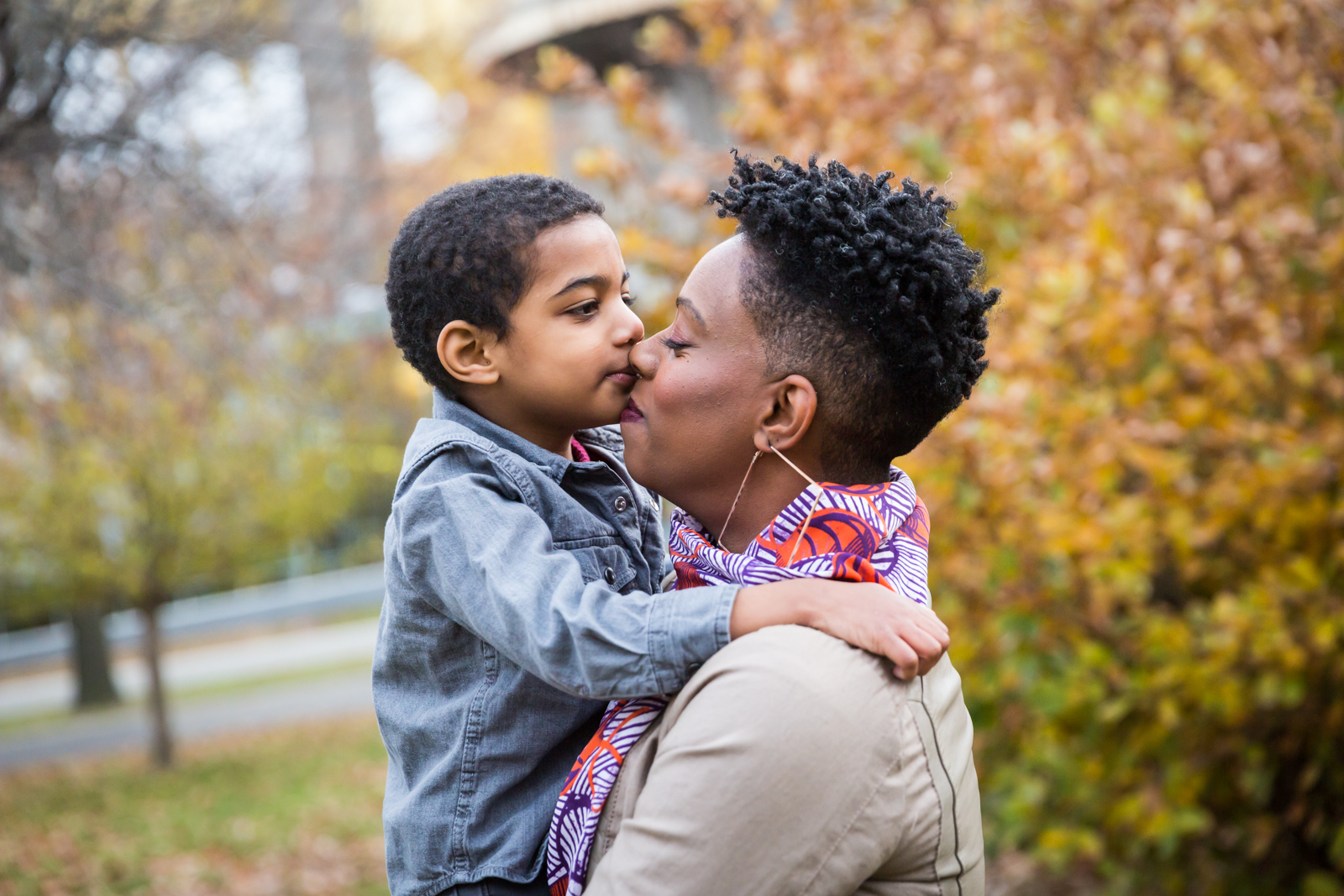 Flushing Meadows Corona Park family portrait of son kissing mother